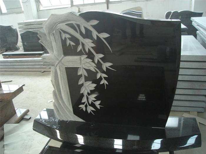 Black granite headstone with tree carving